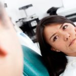 Woman with Pain Holding Her Jaw in Dentist Chair Kennesaw GA